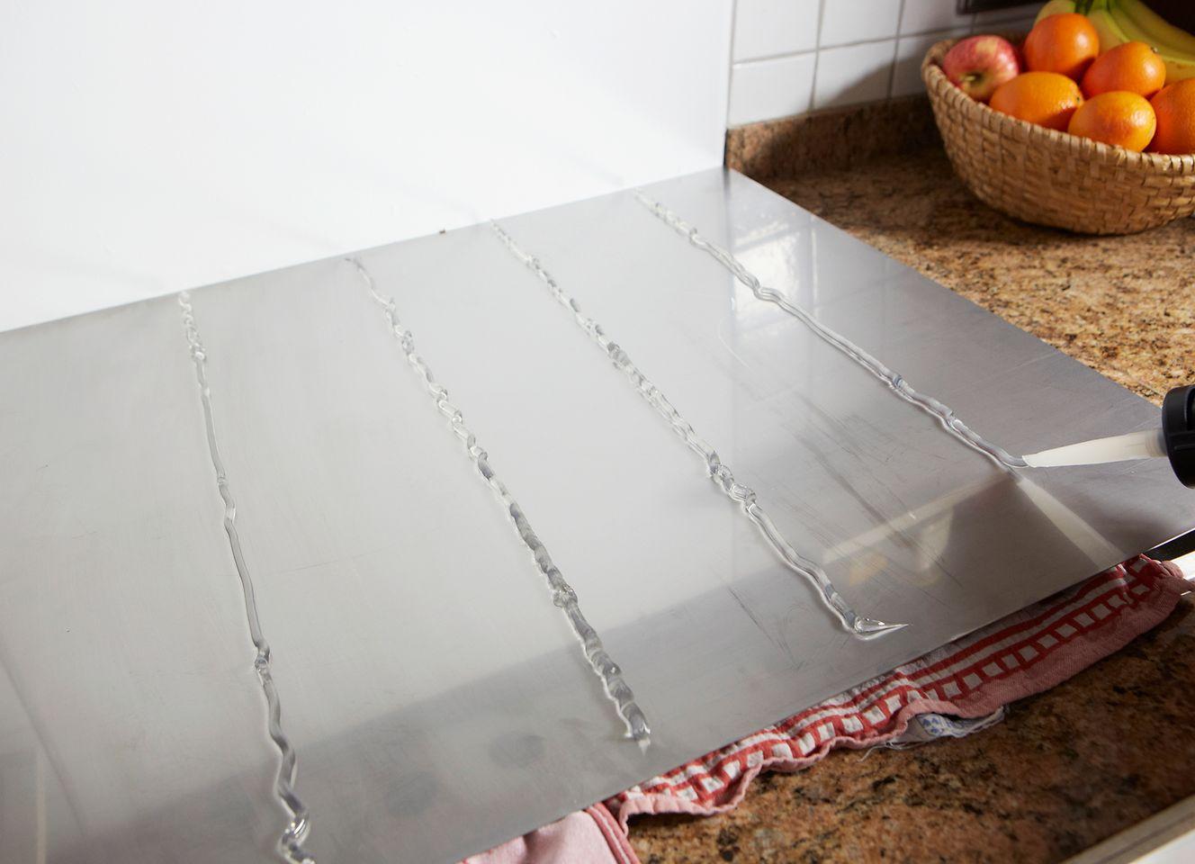 Mit Pattex 100% Kleben und Dichten einen eleganten und funktionalen Spritzschutz einfach selbst in der Küche anbringen.