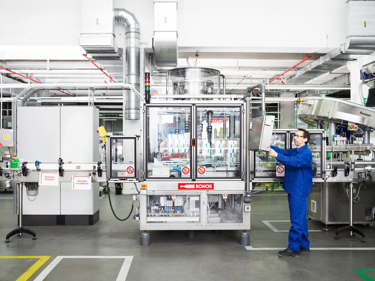 An employee in Duesseldorf is filling detergent at the production line.