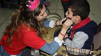 A volunteer princess paints the face of a young boy