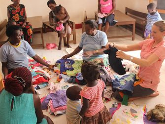 Gabriele Haak and the caretakers sort the donated clothes from Germany according to their size and then distribute them to the children.