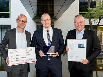 Prof. Dr. Thomas Müller-Kirschbaum (rechts), Leiter der globalen Forschung und Entwicklung im Unternehmensbereich Laundry & Home Care, und Arndt Scheidgen  (links), Leiter der internationalen Produktentwicklung im Unternehmensbereich Laundry & Home Care, überreichen den Laundry & Home Care Research Award 2018 an Dr. Thiemo Faßbach